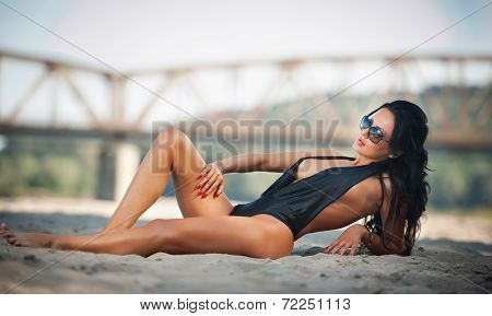Portrait of young sexy brunette girl in black low-cut swimsuit lying on the beach with a bridge