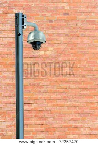Security Camera Against Brown Brick Wall