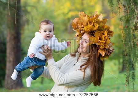 Beautiful Young Woman Holding A Baby Girl In A Park With A Maple Leaf Wreath