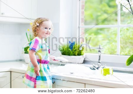 Little Curly Toddler Girl washing dishes, cleaning with a sponge and playing with foam in the sink