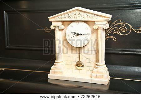 Elegant antique clock. Clock with Greek temple. Marble clock on black piano