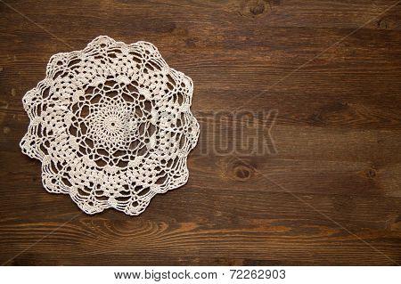 Crochet doily over dark wood