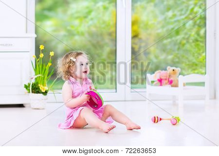 Cute Toddler Girl Playing Tambourine In A White Room With Big Garden View Window