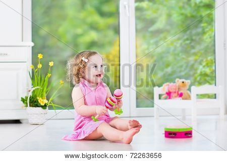 Cute Curly Toddler Girl Playing Tambourine In A Sunny White Room With A Big Window