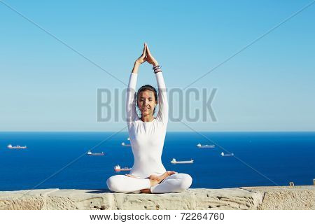 Young healthy woman at sunny day practicing yoga at high altitude on beautiful sea background, happy