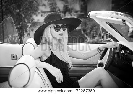 Outdoor summer portrait of stylish blonde vintage woman driving a convertible retro car. Fashionable