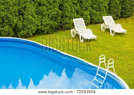 Two lounge chairs by the pool.
