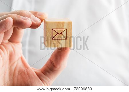 Hand Holding A Wooden Block With An Envelope Icon
