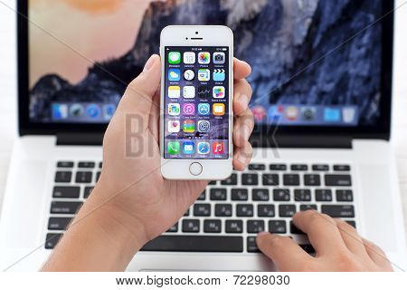 Iphone 5S With Ios 8 In Hand Over Macbook Pro
