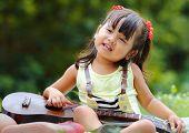foto of ukulele  - Little asian girl was playing ukulele happily in the park - JPG