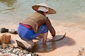 pic of ou  - washing gold in the river woman sieves rock at river Nam Ou in Laos - JPG