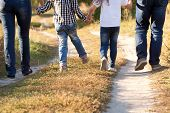 foto of children walking  - Family feet and legs in jeans. Father mother son and daughter walking on the road. Rear view.