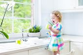 foto of window washing  - Cute curly toddler girl in a colorful dress washing dishes - JPG
