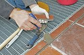 image of grout  - worker repairing and grouting patio tiles outdoors - JPG