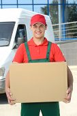stock photo of moving van  - Smiling young male postal delivery courier man in front of cargo van delivering boxes - JPG