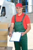 pic of moving van  - Smiling young male postal delivery courier man in front of cargo van delivering boxes - JPG
