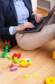 picture of superwoman  - Woman sitting on floor and typing on laptop surrounded by kids toys - JPG