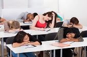 stock photo of students classroom  - Bored female college student with classmates sleeping at desk in classroom - JPG