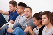 stock photo of classmates  - Portrait of happy male college student sitting with classmates against wall in classroom - JPG