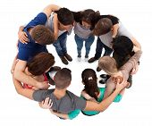 foto of huddle  - High angle view of young university students forming huddle against white background - JPG
