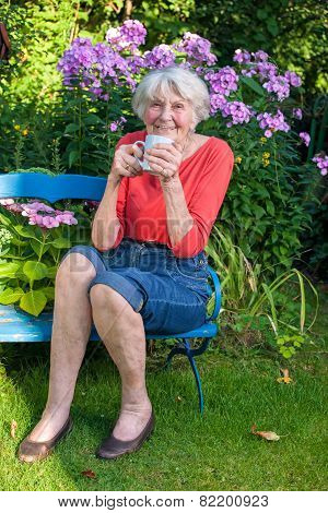 Happy Old Woman Having A Coffee At The Garden