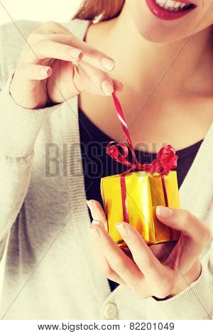 Beautiful woman unwrapping small present held in her hands.