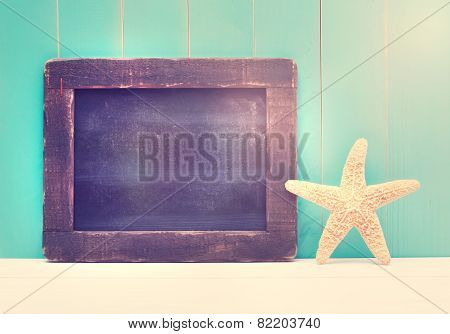 Starfish And Small Chalkboard On A Teal Colored Wooden Background