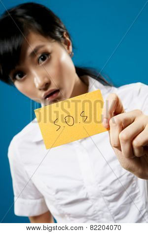 SOS, closeup portrait of Asian business woman on studio blue background.