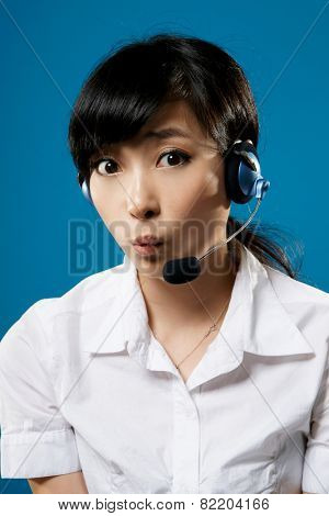 Hotline, closeup portrait of Asian business woman on studio blue background.