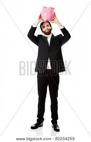 Handsome businessman searching money in piggybank.