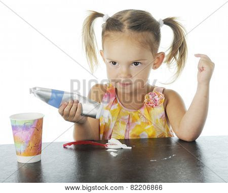 Closeup view of an adorable preschooler smugly looking up as she squeezes toothpaste on her brush.  On a white background.