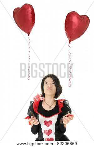A young teen Valentine girl sadly watching two heart-shaped balloons rising in their separate ways.  On a white background.