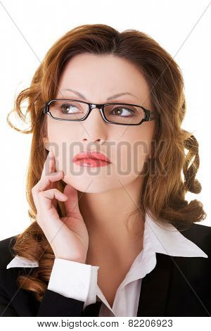 Thinking business woman with hand on chin looking up.