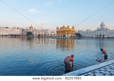 Sikh Men Bath In The Holy Lake At Golden Temple In The Early Morning. Amritsar. India