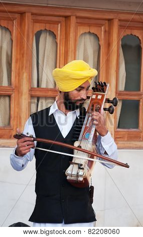 Indian Musician Playing Sarangi In Golden Temple In Amritsar. India