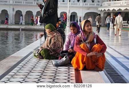 Indian Women Sitting Near The Lake At Golden Temple. Amritsar. India