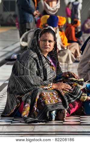 Indian Woman With Child Sitting Near The Lake At Golden Temple. Amritsar. India