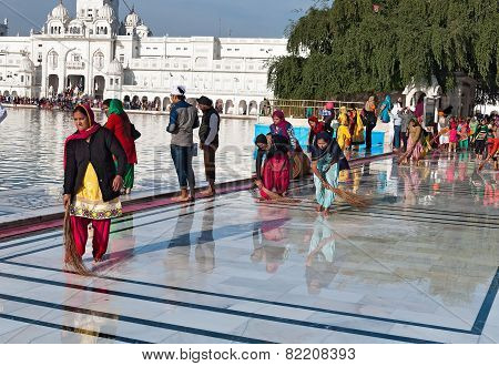 Indian Women Clean Floor Near Golden Temple Before The Evening Prayer. Amritsar