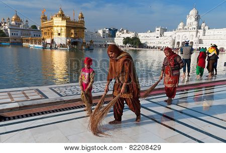 Indian Women And Children Clean Floor Near Golden Temple Before The Evening Prayer. Amritsar
