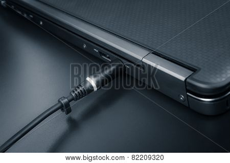 Close Up Of Battery Charge On Laptop Computer With Power Plug