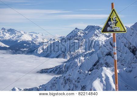 danger steep cliff mountain sign, mountains and blue sky above clouds, Krasnaya Polyana, Sochi, Russia