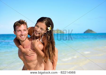 Beach couple vacation fun - happy piggyback. Cute mixed race asian chinese woman piggybacking on the back of handsome caucasian man laughing in love during summer holidays or vacations in Hawaii, USA.