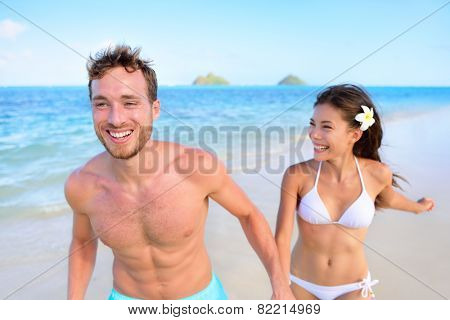 Happy couple having fun on beach vacation during summer holiday. Multiracial fit couple running together holding hands laughing in the sun. Young adults in shape carefree feeling good in their body.