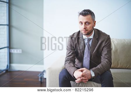 Confident employer in suit looking at camera