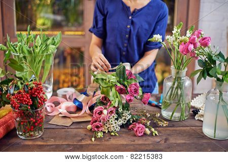 Female florist tying flowers up with decorative ribbon at workplace