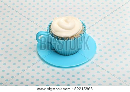 Sweet dessert, cupcake  with butter cream over spotted background.