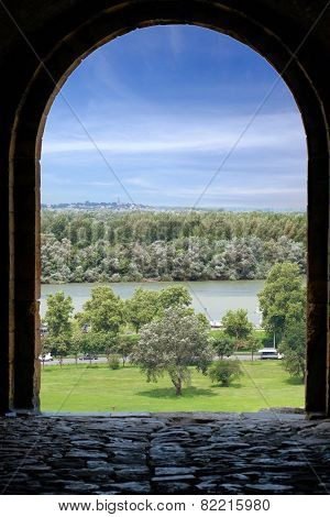 an arch stone Kalemegdan fortress frames the view of the river Danube, Belgrade Old Town