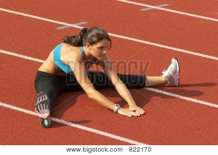 Young Woman in Sports Bra Stretching Legs on Track