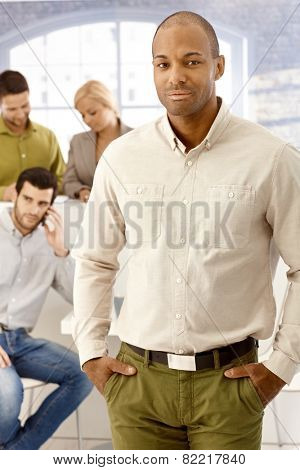 Portrait of confident young afro-american businessman standing with hands in pockets.