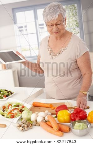 Contemporary grandmother cooking healthy food, using tablet computer to prepare meal.